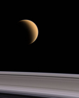 Titan, a moon of Saturn, rises above the rings of Saturn. Image courtesy of NASA/JPL